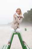 Alone on the beach. Freezing girl sitting alone on the beach Royalty Free Stock Image