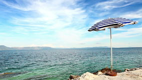 Alone beach retro style umbrella on the croatian shore Stock Photography
