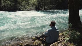 Alone bearded man is sitting on shore and pensively looking on river at day. Adult thinking man is sitting on coast of river in forest. He is resting and stock video footage
