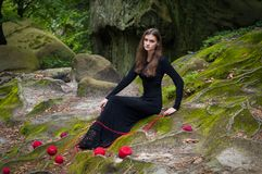 Alone beautiful girl is sitting on green moss in a fairy forest. royalty free stock photography