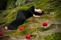 Portrait of a brunette in a black dress that lies on the green moss, and around scattered balls of red thread. royalty free stock photos