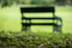 Alone bench in the green yard, blur and defocus Stock Images