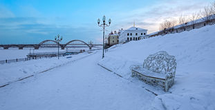 Alone bench on Volga River embankment, Rybinsk. Alone bench on snow covered promenade over frozen Volga River in the city of Rybinsk at cold winter sunrise Stock Image