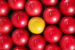 Alone billiard yellow ball between many red balls Stock Photography