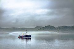 Alone boat driving through in the foggy sea in the scottish highlands. Alone boat driving through in the foggy sea in the Highlands of Scotland Royalty Free Stock Image