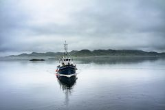 Alone boat driving through in the foggy sea in the scottish highlands. Alone boat driving through in the foggy sea in the Highlands of Scotland Royalty Free Stock Photos