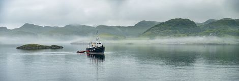 Alone boat driving through in the foggy sea in the scottish highlands. Alone boat driving through in the foggy sea in the Highlands of Scotland Stock Photography
