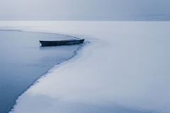 Alone boat on frozen lake Stock Photo