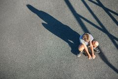 Alone boy without friends sits on skateboard. Child loneliness c stock photos