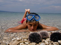 Alone boy in sea with sea urchins. Alone boy lying in Adriatic sea with diving mask and a lot of a sea urchin stock photos