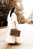 Alone bride at the road. With old suitcase Stock Photography