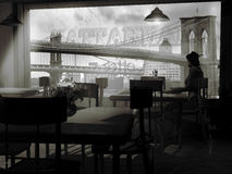 Alone at the cafe. Monochrome image of a woman, in the fifties, sitting at a table in a cafe close to the East River, Manhattan, waiting for someone who does not Royalty Free Stock Images