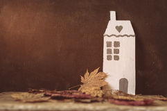 Alone cardboard house and dry leaves Royalty Free Stock Images