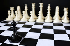 Alone chess pawn in front of enemy team. Courage and boldness Stock Photo