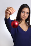 Alone on Christmas. Young woman holding single red christmas ball Royalty Free Stock Images