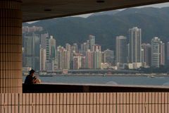 Alone in the City. Man eating a meal and enjoying the view of Victoria Harbor and the Hong Kong skyline Stock Photo