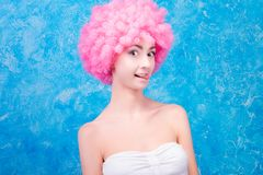 Comic girl with pink wig. Alone comic female / woman / girl with pink curved wig on blue background with cheeky emotion. Clown concept stock photography