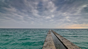 Alone concrete pier with clear ocean and stormy clouds Stock Photo