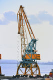 Alone Crane on a port. Massive blue and orange crane in harbour Royalty Free Stock Image