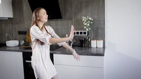 Alone crazy brunette woman is wearing pajamas and dancing in kitchen in evening, shaking her hands and body