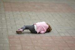 Alone crying girl lying on asphalt Stock Photo