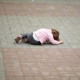 Alone crying girl lying on asphalt. Alone crying little girl lying on asphalt Stock Photo