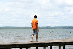 Alone on the Dock. A young single latino man alone on a dock Stock Photography