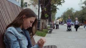 Alone serious Girl sitting on the bench and texting with mobile phone in jeans. Alone Female serious Girl sitting on the wooden bench and texting flip through stock video