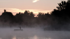 Alone in the fog. A boatman swims through the lake in the fog stock image