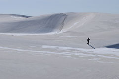 Alone in a Fragile Land. A person walks alone in the vast expanse of the white sands desert. An excellent image to portray lonliness, solitude, adventure, or stock photography