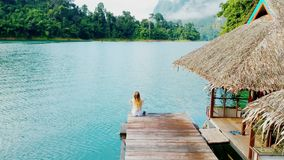 Alone girl on pier. Luxurious over-water villas on tropical island resort. Aerial footage. stock footage