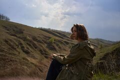 Alone girl is sad on nature hills background. Young woman isolated outdoor, post apocalyptic, epidemic, home violence