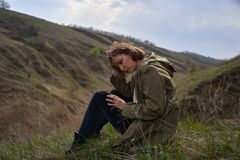 Alone girl is sad on nature hills background. Young woman  outdoor, post apocalyptic, epidemic, home violence