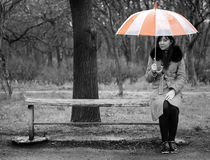 Alone girl sitting at bench Stock Photo