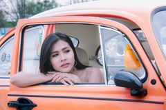 Alone girl sitting in the car and looking for waiting someone.  Stock Photo