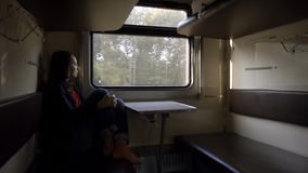 Girl tourist is looking out the train window. Alone girl tourist in empty train compartment is looking out the window. fast train stock video footage