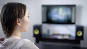Alone girl is watching tv sitting in a living room of her house in evening, concentrated following the plot of movie. View through shoulder, display is blurred stock footage