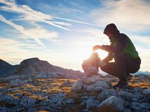 Alone hiker man on the top of the Alpine mountain building pyrmid from pebbles. Royalty Free Stock Photography