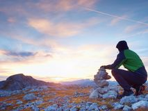 Alone hiker man on the top of the Alpine mountain building pyrmid from pebbles. Stock Photo