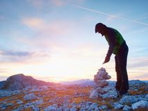 Alone hiker man on the top of the Alpine mountain building pyrmid from pebbles. Royalty Free Stock Images