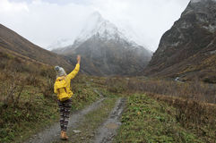 Alone hiker in mountains. Young woman hiker in yellow clothing walking in valley to snowy mountains at rainy weather Royalty Free Stock Image