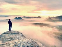 Alone hiker in red cap stand on peak of sandstone rock in rock empires park and watching over the mist Royalty Free Stock Photography