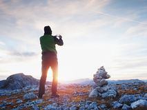 Alone hiker takes phone photo in mountains. Man on Alps mountain peak.View to purple sky Royalty Free Stock Photo