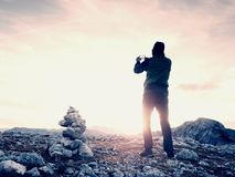 Alone hiker takes phone photo in mountains. Man on Alps mountain peak.View to purple sky Royalty Free Stock Photography
