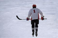 Alone hockey player going to slash puck at outdoor skating rink. stock images