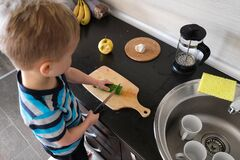 Alone Independence Vegetarian Child Cuts Green Cucumber With Knife In Kitchen, Vegan Kid Montessori Training, Side View Stock Image