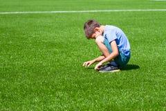 Sad alone kid sitting on the football field royalty free stock photo