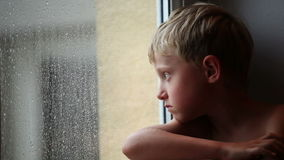 Alone little boy looks raindrops through window glass Stock Images