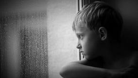 Alone little boy looks raindrops through window glass stock video