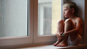 Alone little boy looks raindrops through window glass stock video footage